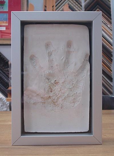 Gipsafdruk van een hand verdiept ingelijst